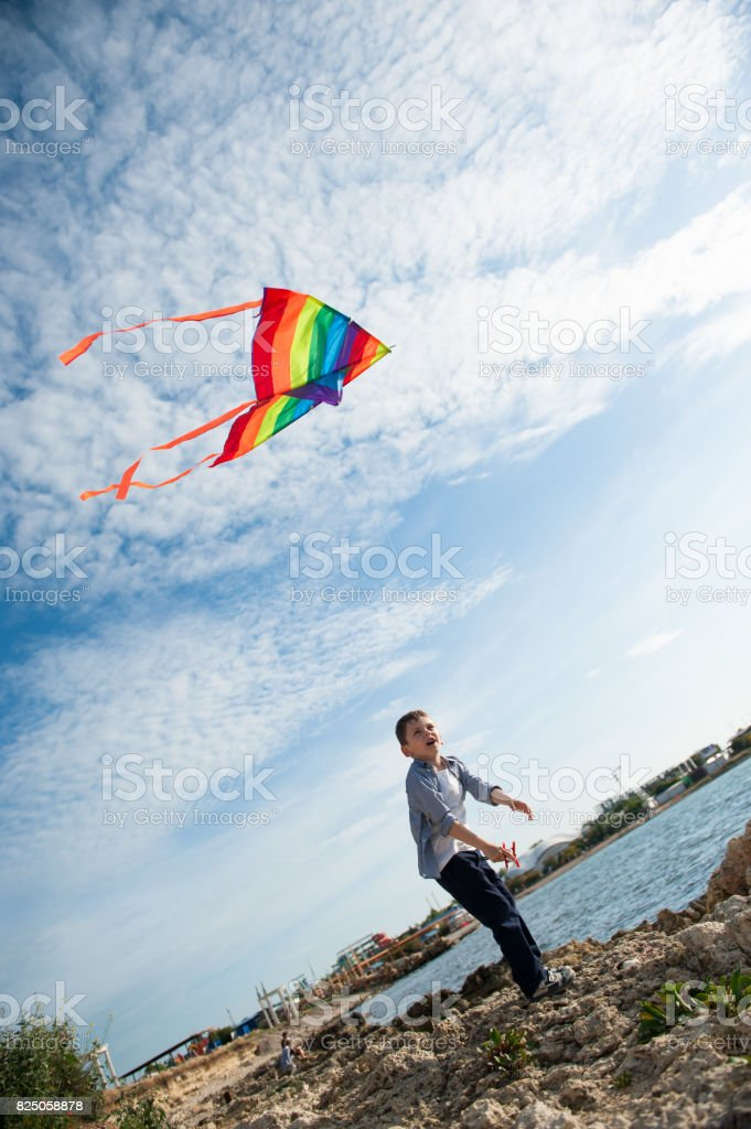 happy cute kid holding a kite flying in the sky on the background of sea stock photo