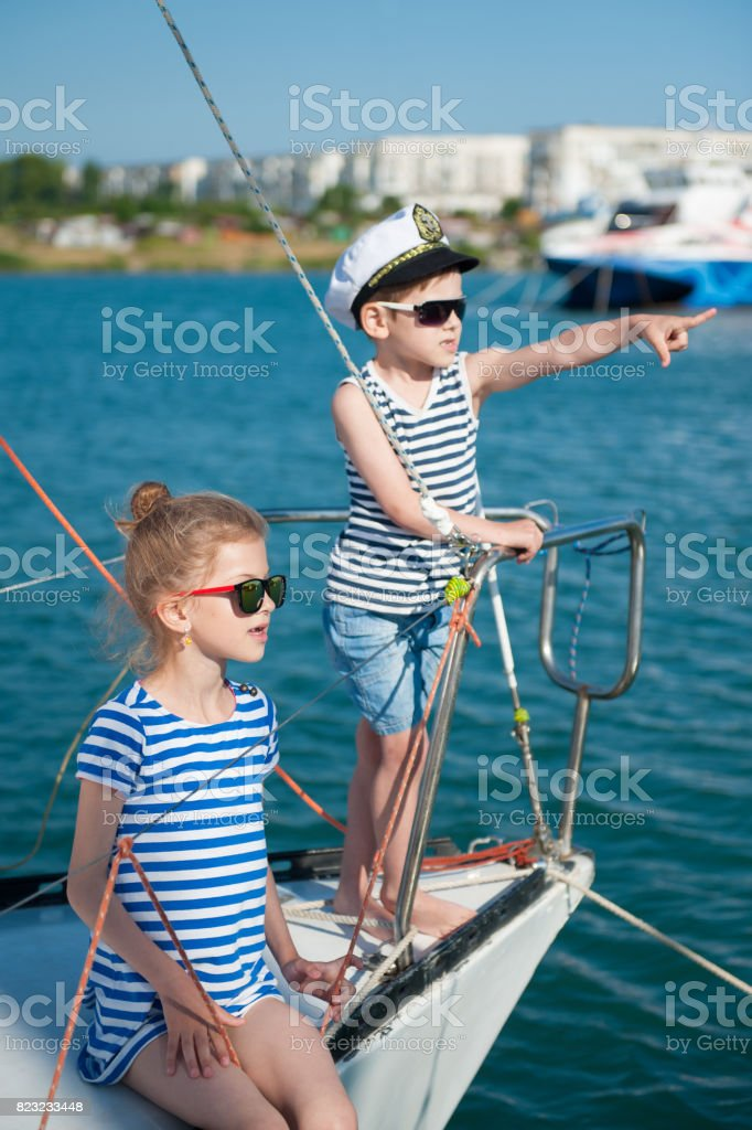 happy cute kids aboard luxury yacht in summer sunny day in port stock photo