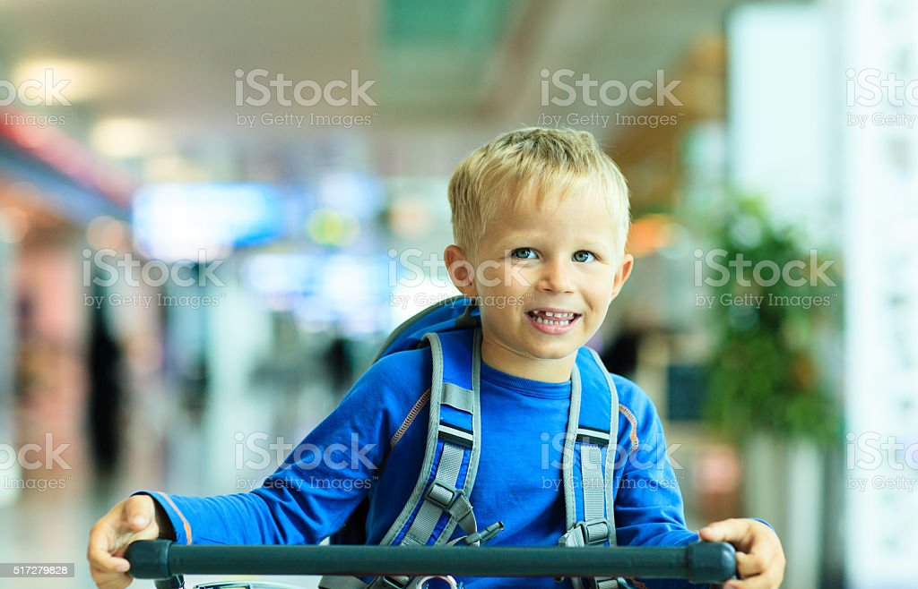 Happy cute little boy at airport riding on luggage cart stock photo