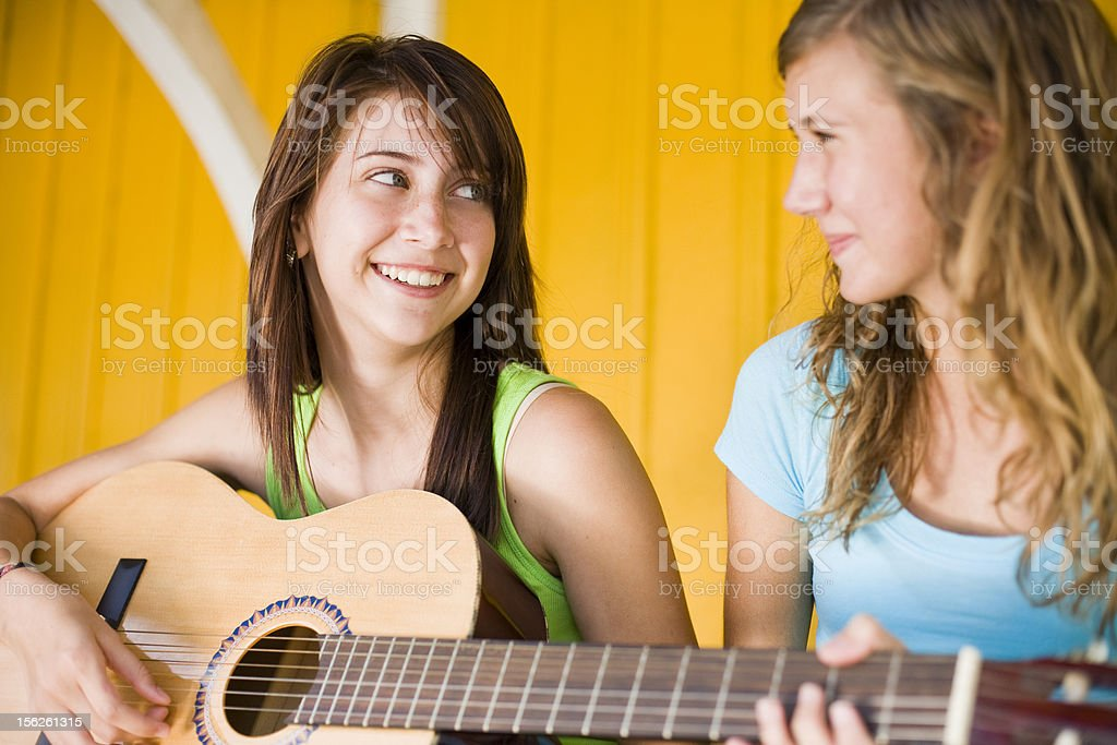 Happy cute  teenage girls playing the guitar royalty-free stock photo