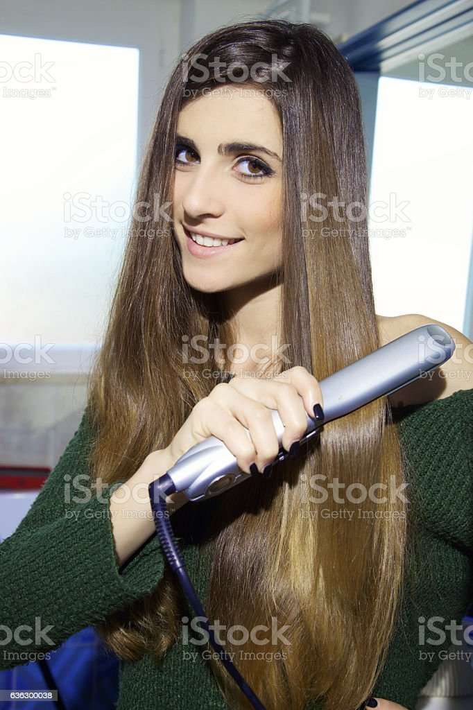 Happy cute young woman straightening long silky hair stock photo