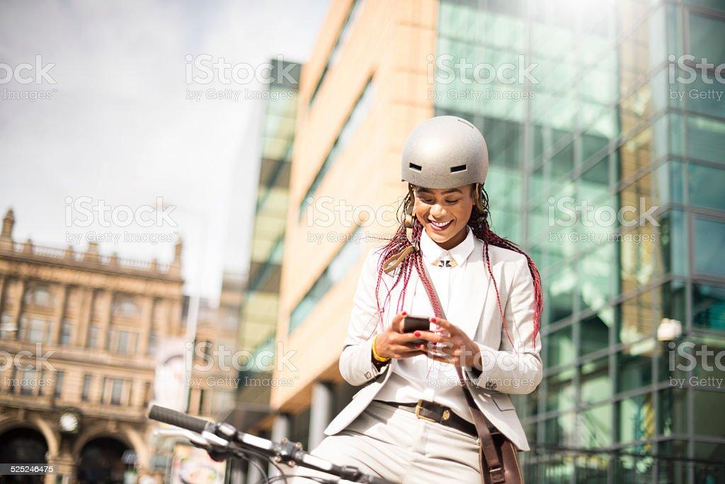 happy cyclist checks her phone stock photo