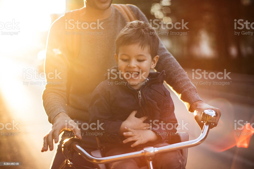 Father and his son cycling together outdoors on a beautiful sunny...