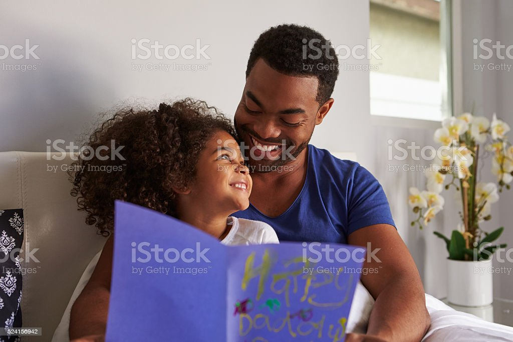 Happy dad and daughter in bed with card on birthday stock photo