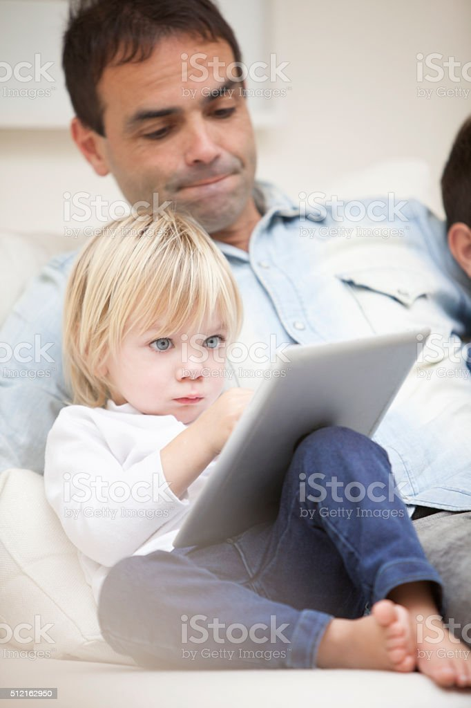 Happy dad and kids playing with tablet stock photo