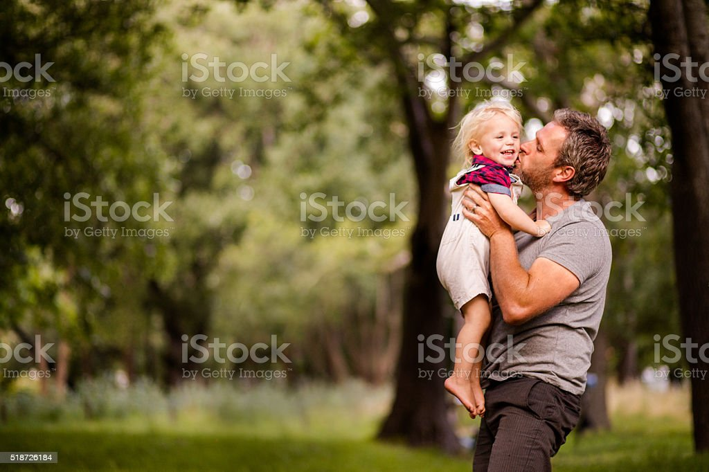 Happy dad kissing his laughing son at the park stock photo