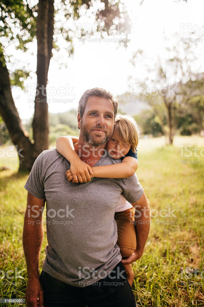 Happy dad piggybacking his son at the park stock photo