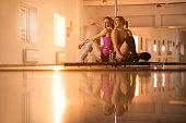 Happy dancers communicating on a break in dance studio.