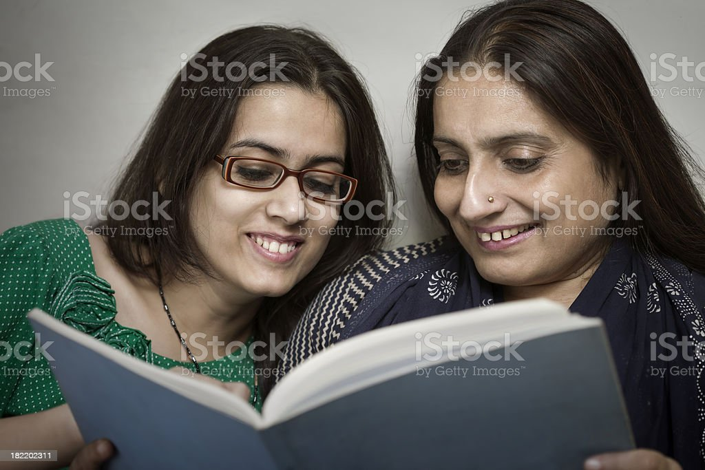 Happy daughter and mother reading a book stock photo