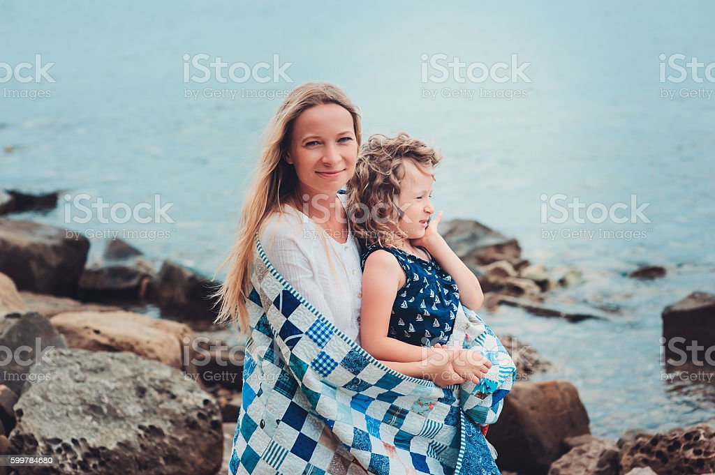 happy daughter holding mother hand on the beach stock photo
