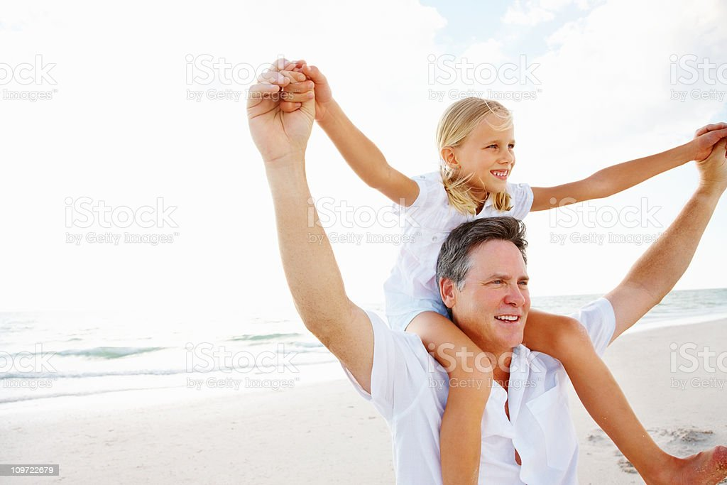 Happy daughter on father's shoulder enjoying at beach royalty-free stock photo