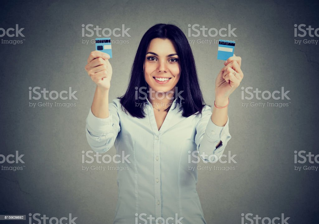 Happy debt free woman holding a credit card cut in two pieces stock photo