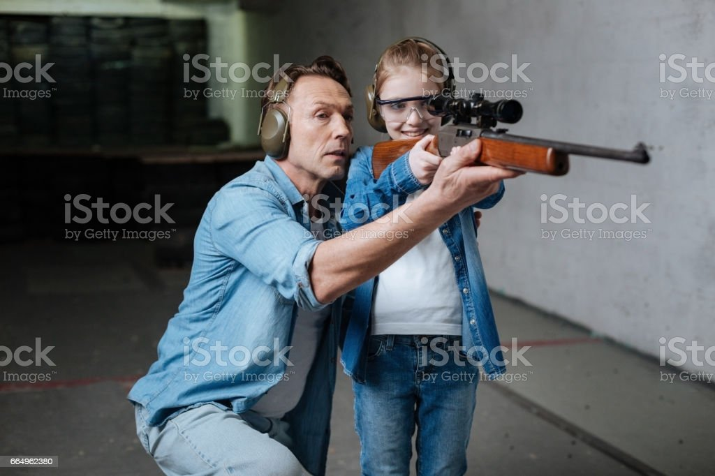 Happy delighted girl looking into the optical sight stock photo