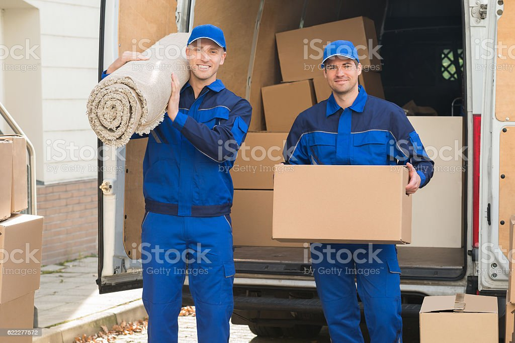 Happy Delivery Men Carrying Cardboard Box And Carpet stock photo