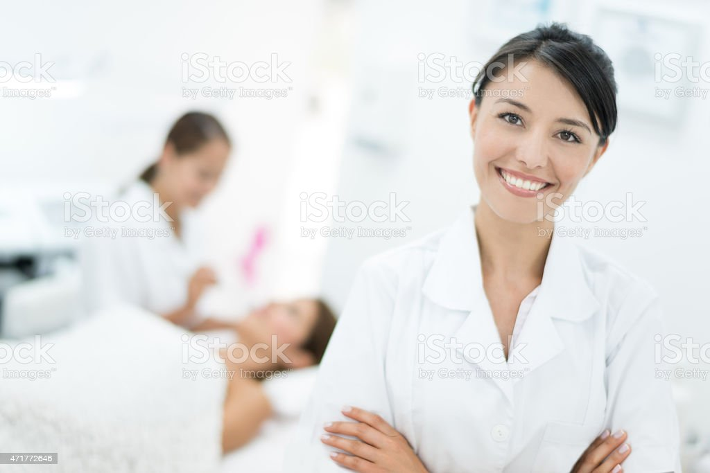 Happy dermatologist at her practice stock photo