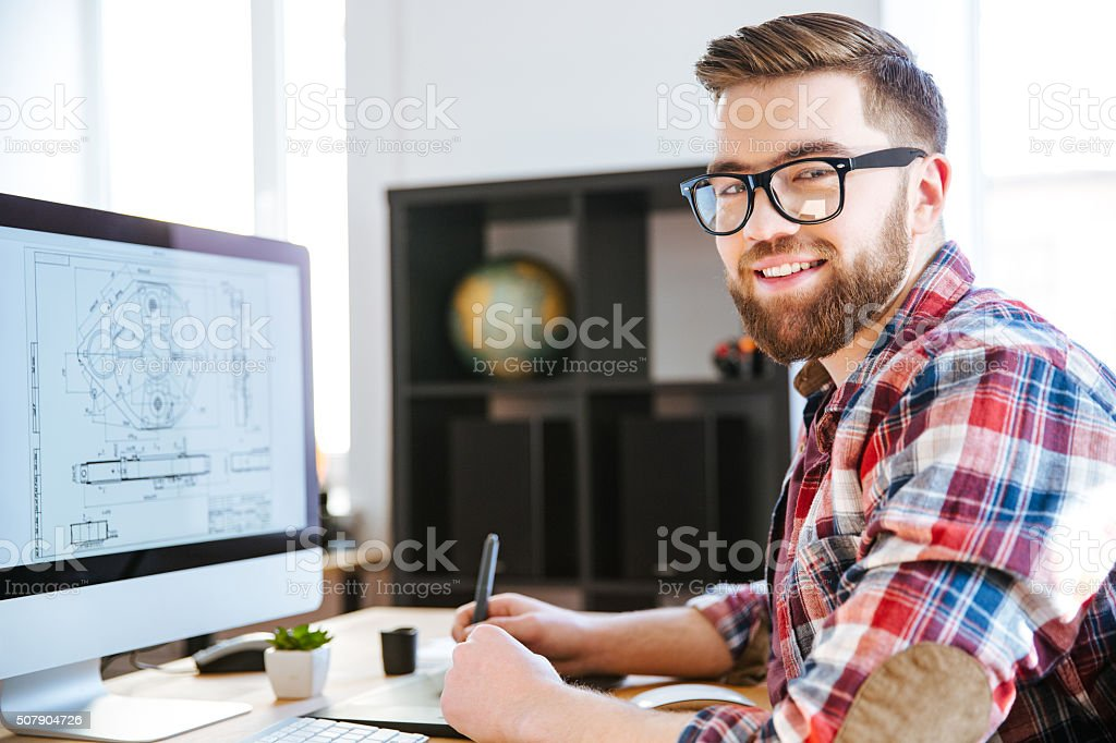 Happy designer drawing blueprint on computer using pen tablet stock photo
