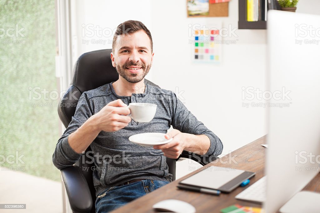 Happy designer drinking coffee at work stock photo