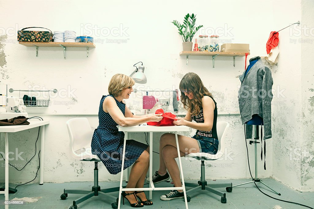 Happy designers working on sewing machine. stock photo