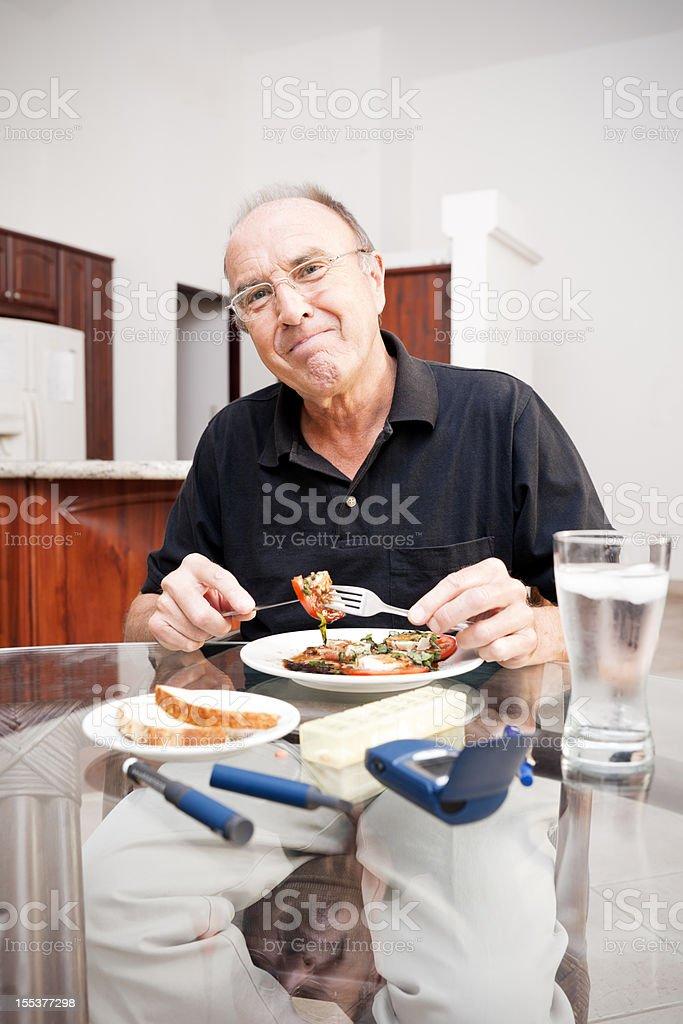 Happy diabetic senior enjoying a healthy meal stock photo