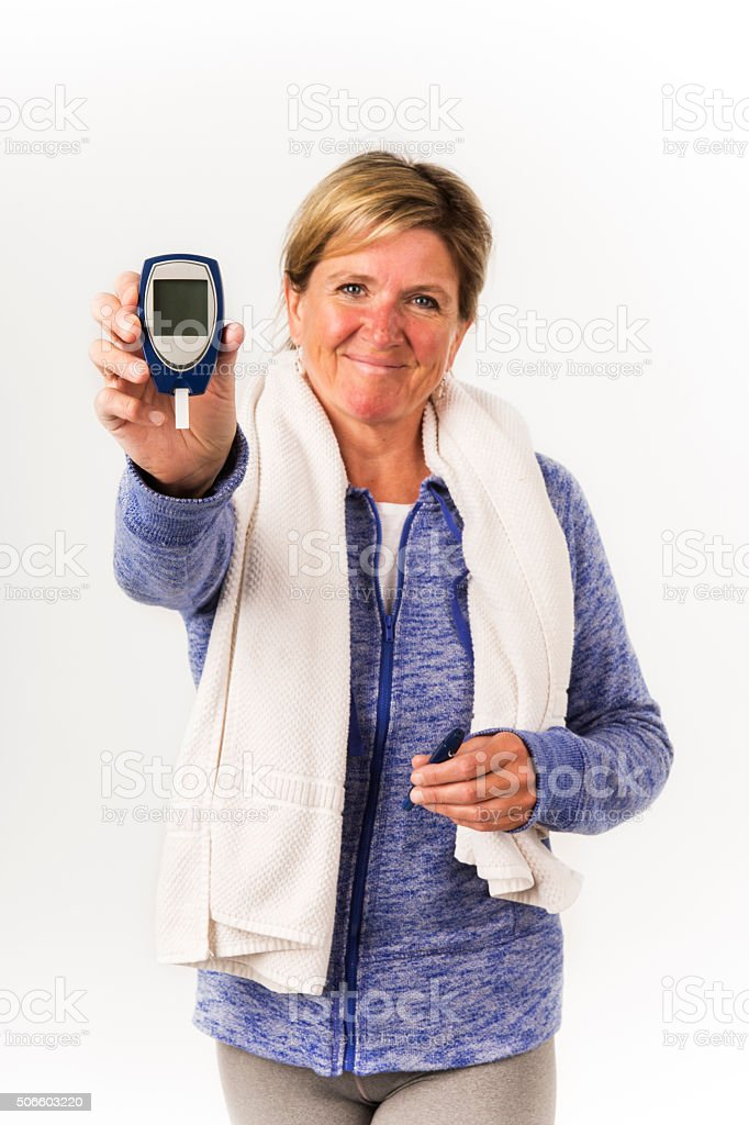Happy, diabetic woman holding up a glaucometer. stock photo