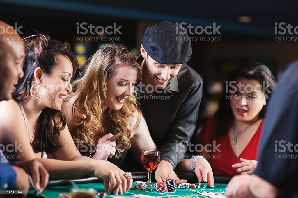 Happy diverse group of friends at blackjack table in casino royalty-free stock photo