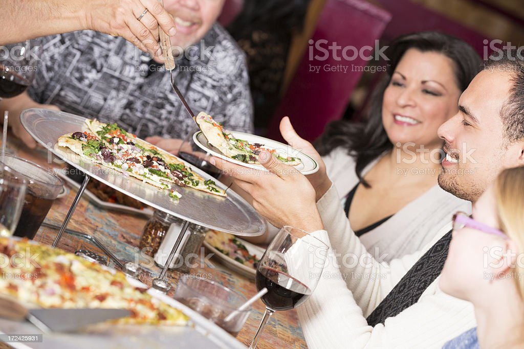 Happy diverse  group of friends sharing pizza at the restaurant royalty-free stock photo