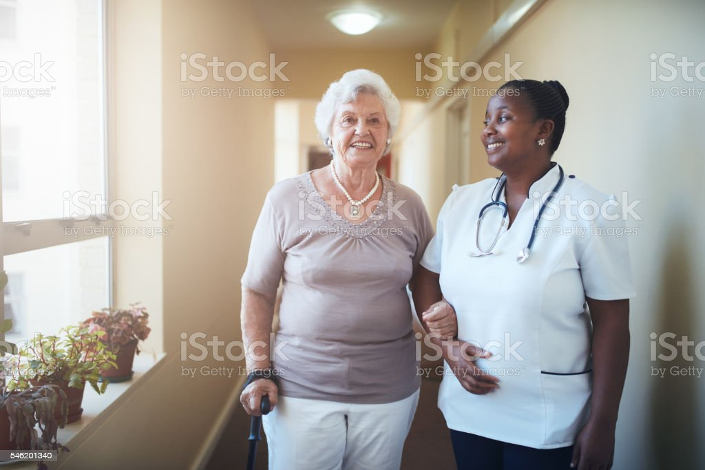 Happy doctor and patient together at nursing home stock photo