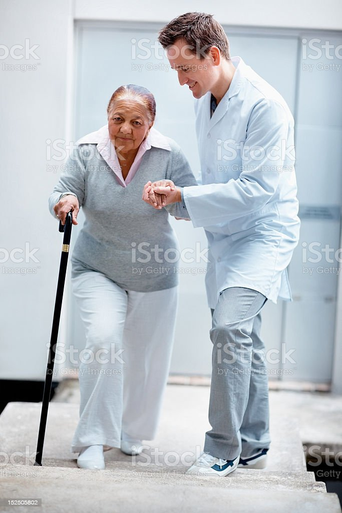 Happy doctor assisting his patient while walking stock photo