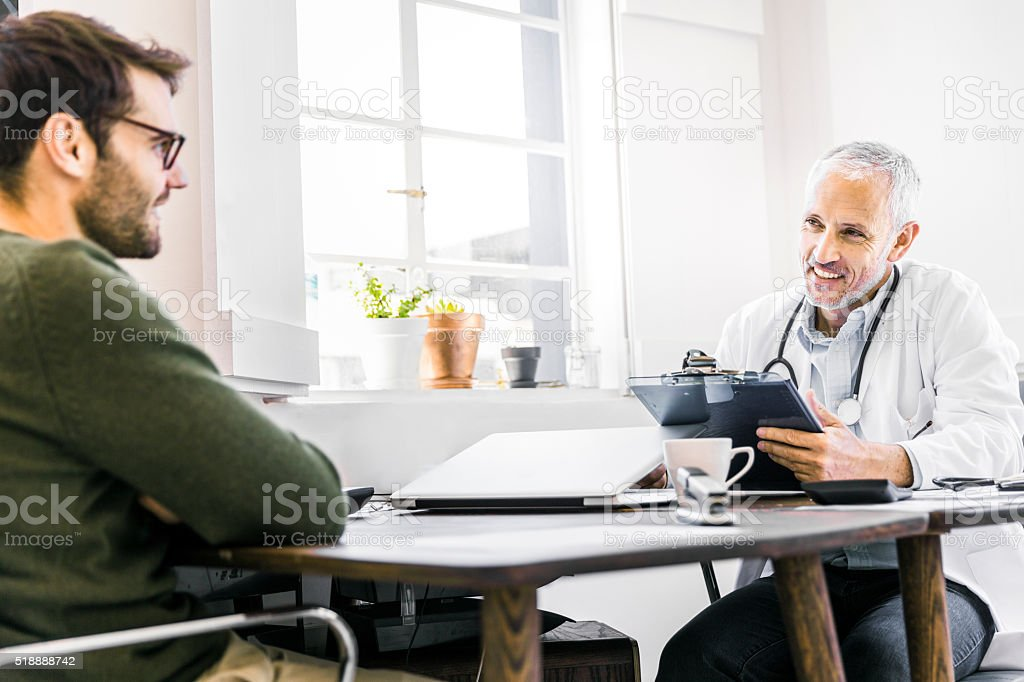 Happy doctor discussing with patient in clinic stock photo