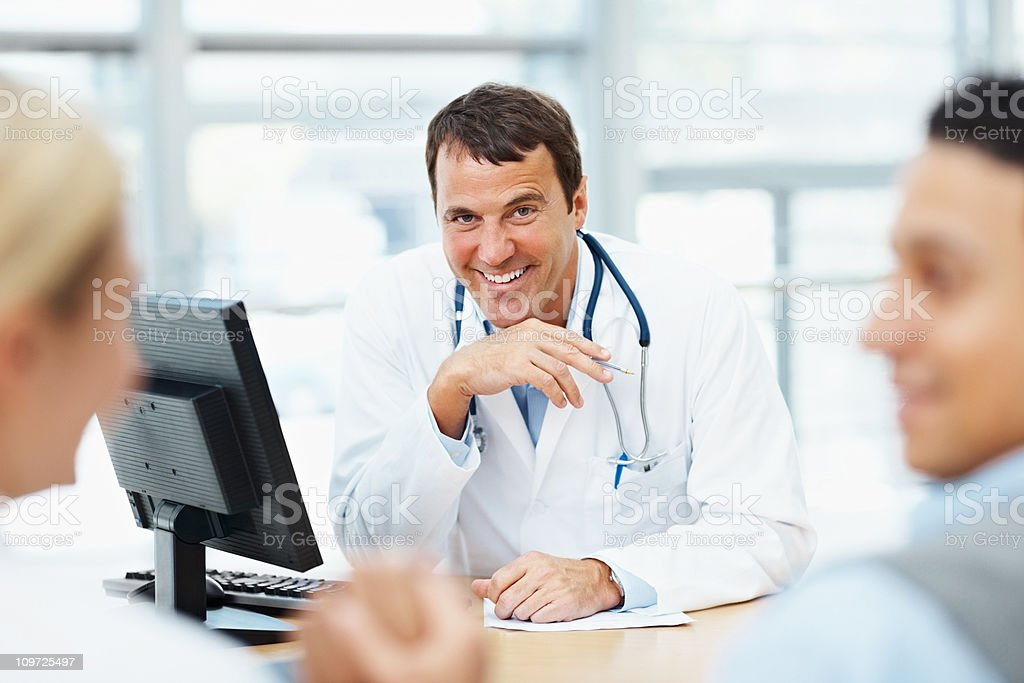 Happy doctor having a discussion with patients royalty-free stock photo
