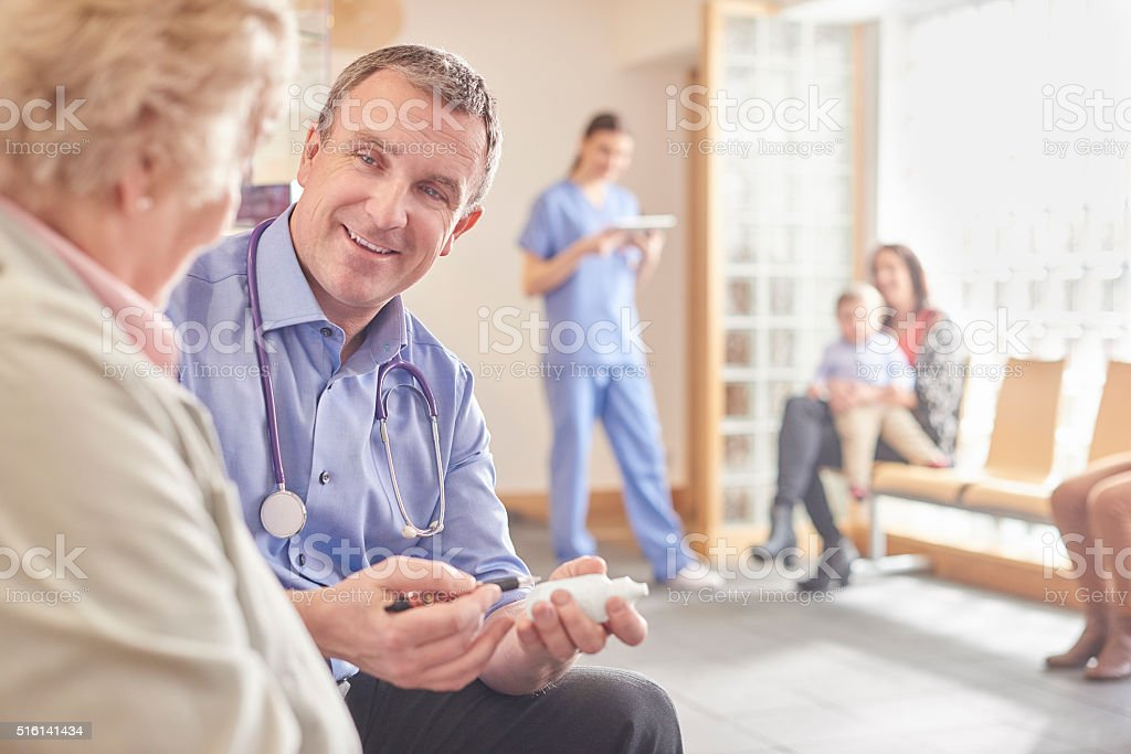happy doctor in his waiting room stock photo