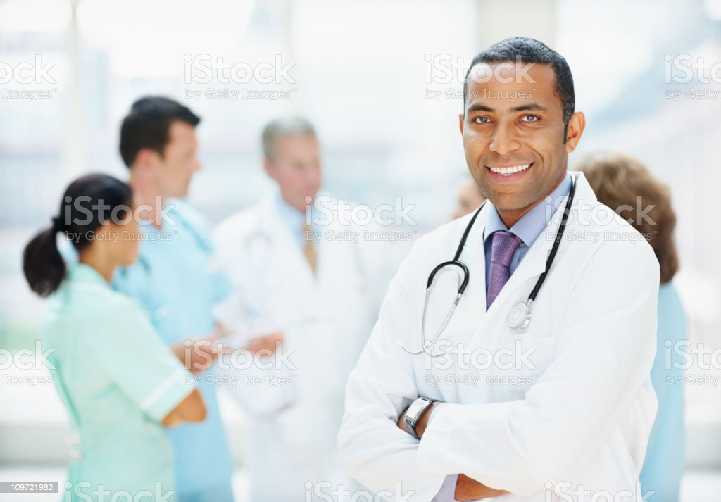 Happy doctor smiling and his blurred team in background royalty-free stock photo