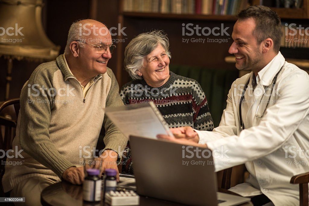 Happy doctor talking to senior couple about some medical documents. stock photo