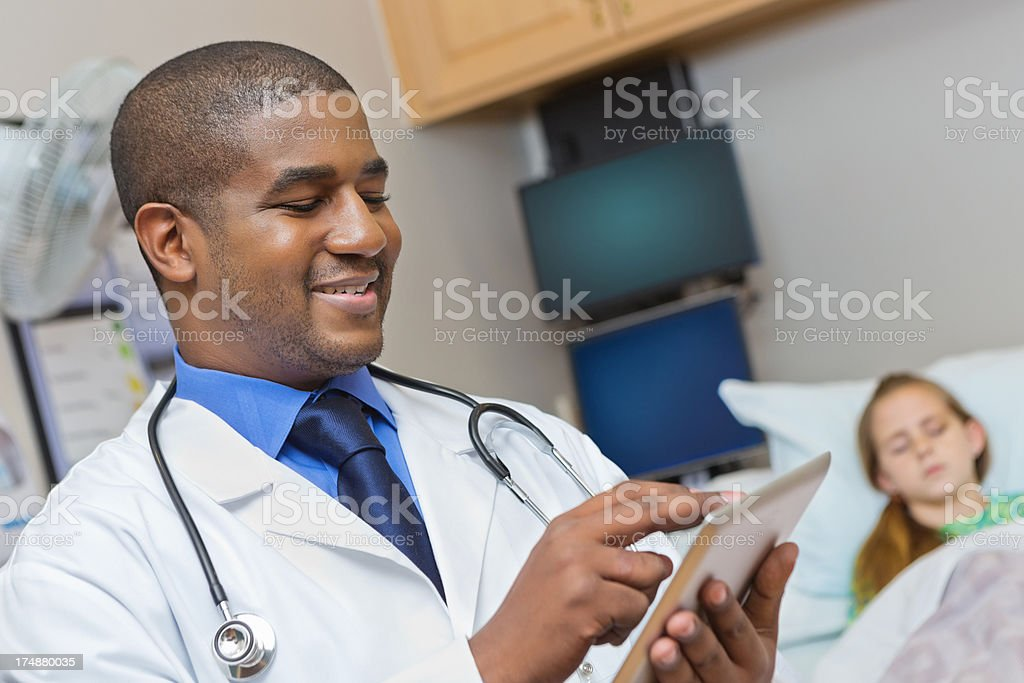 Happy doctor using digital tablet in hospital patient room royalty-free stock photo