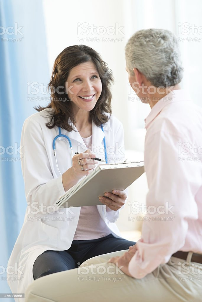 Happy Doctor With Clipboard Looking At Patient stock photo