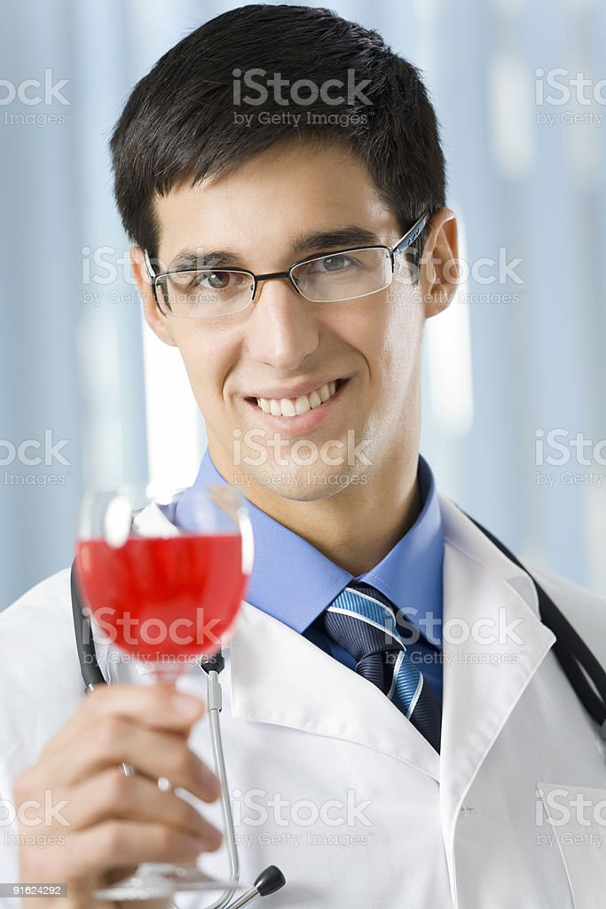 Happy doctor with glass of wine at office royalty-free stock photo
