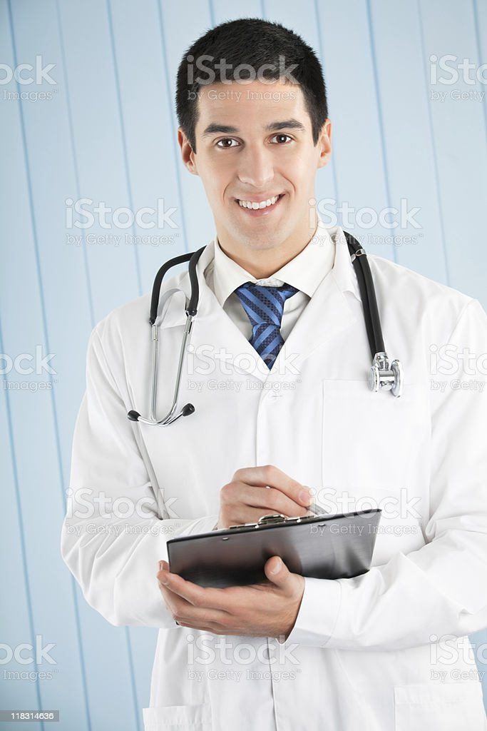 Happy doctor with pen and clipboard at office royalty-free stock photo