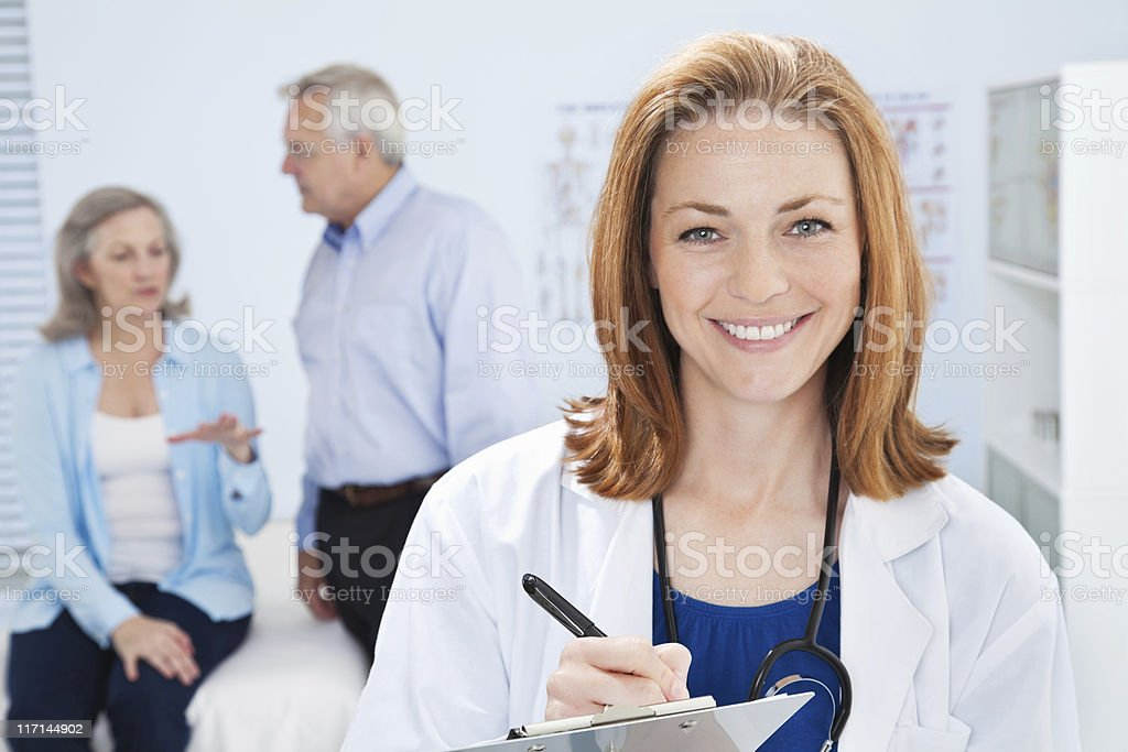 A happy doctor writing notes with  senior patient royalty-free stock photo