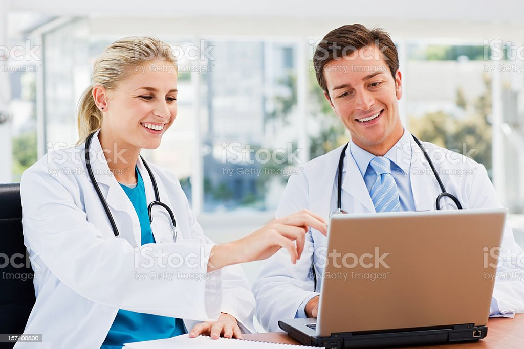 Happy doctors working on a laptop royalty-free stock photo