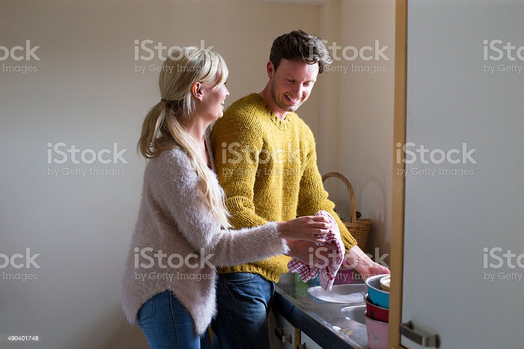 Happy doing the dishes together. stock photo