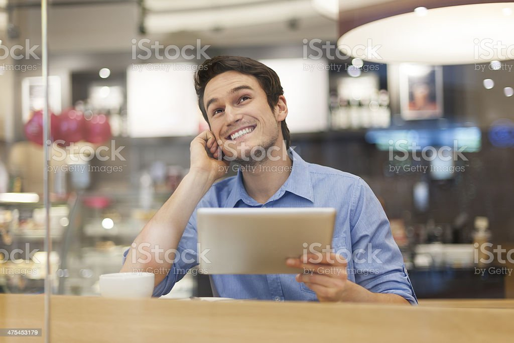 Happy dreaming man with digital tablet in cafe royalty-free stock photo