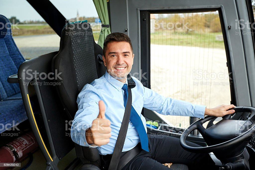 happy driver driving bus and snowing thumbs up stock photo