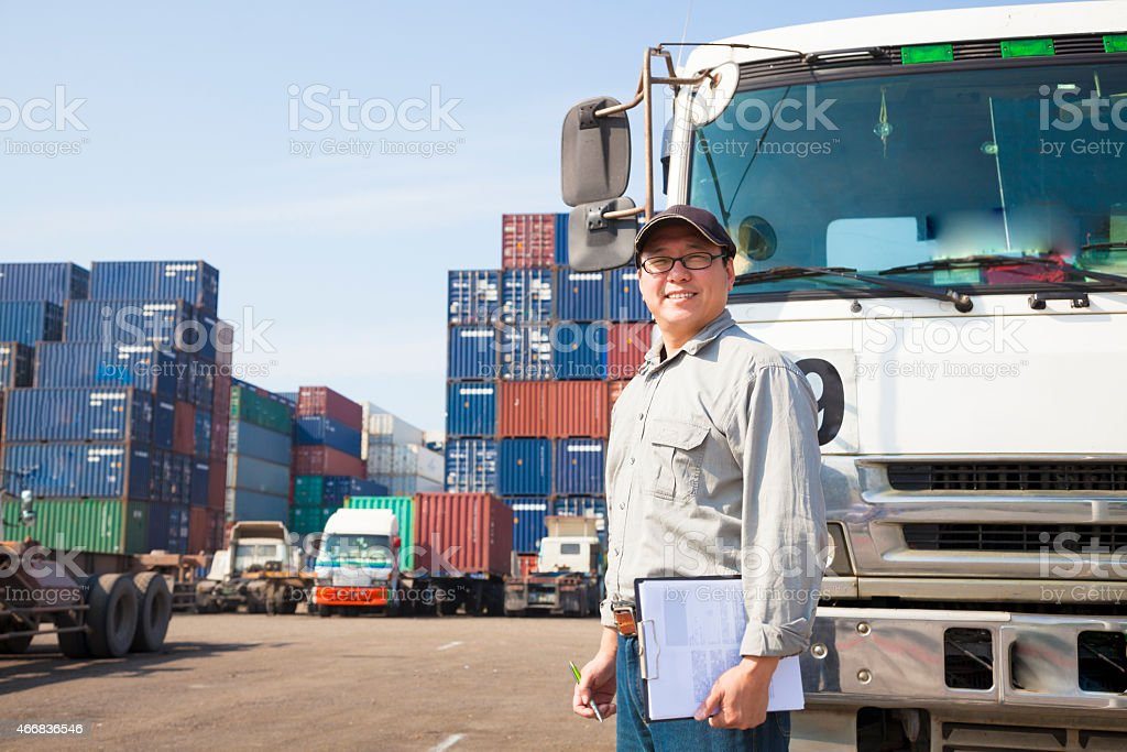 happy driver in front of container truck stock photo