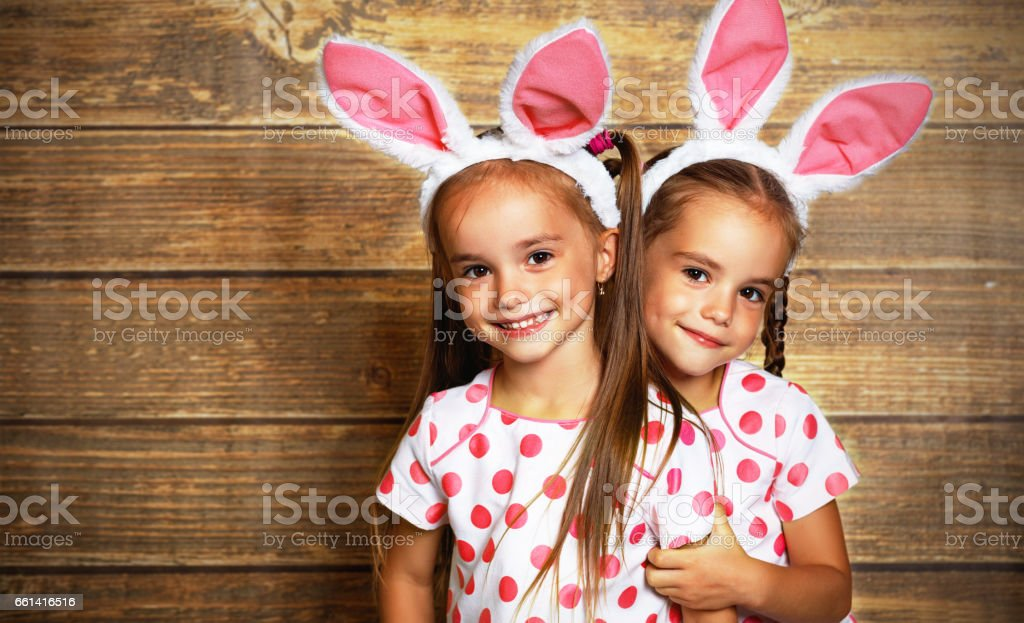 Happy easter! cute twins girls sisters dressed as rabbits  on wooden background stock photo