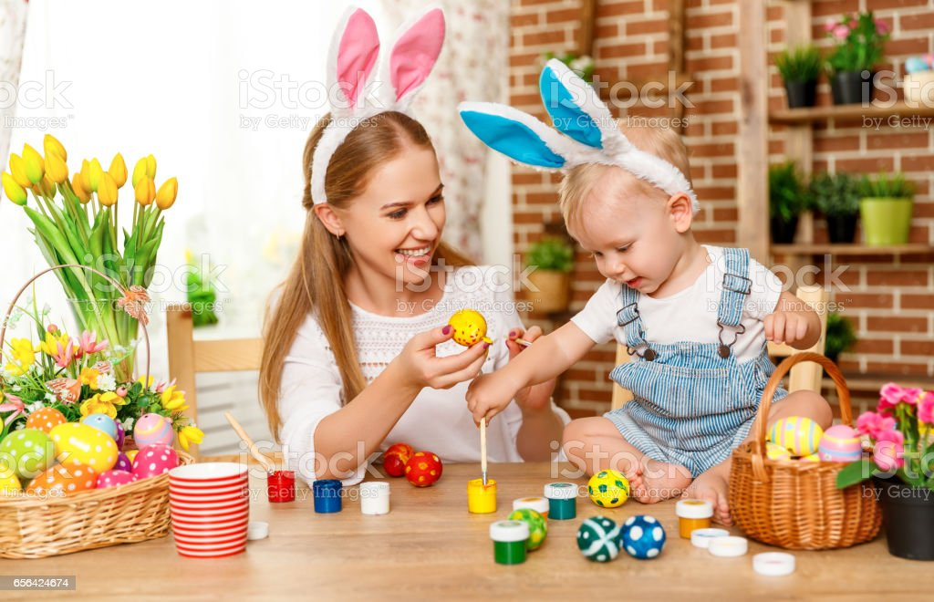 Happy easter! family mother and baby son paint eggs for holiday...