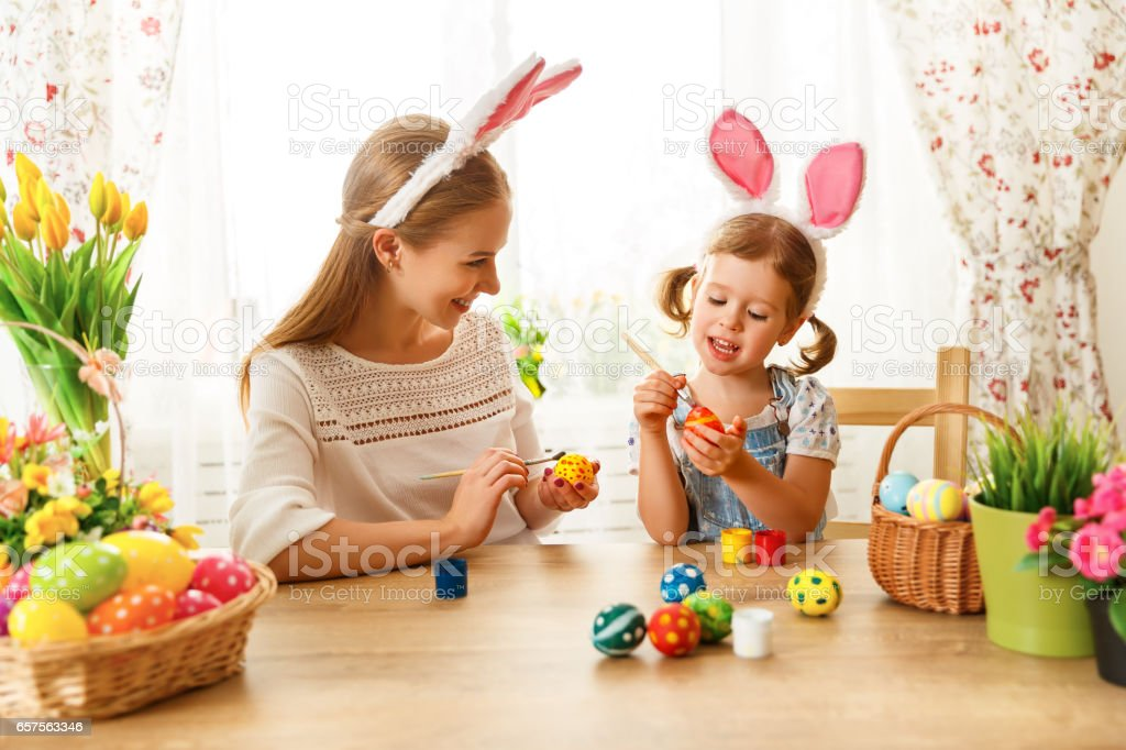 Happy easter! family mother and child daughter paint eggs for holiday...