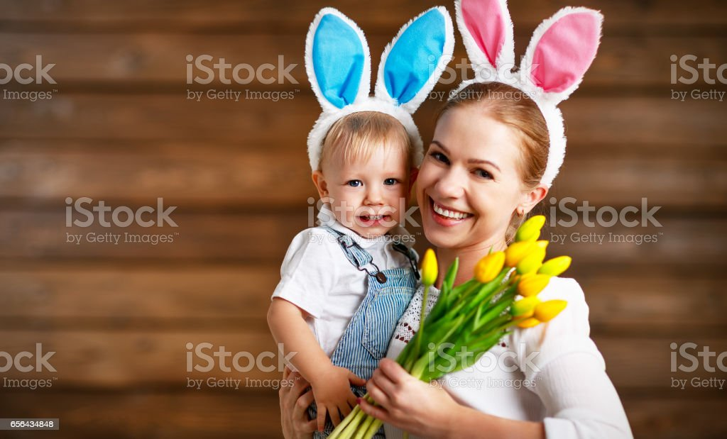Happy easter! mother and baby in rabbit ears with yellow flowers stock photo