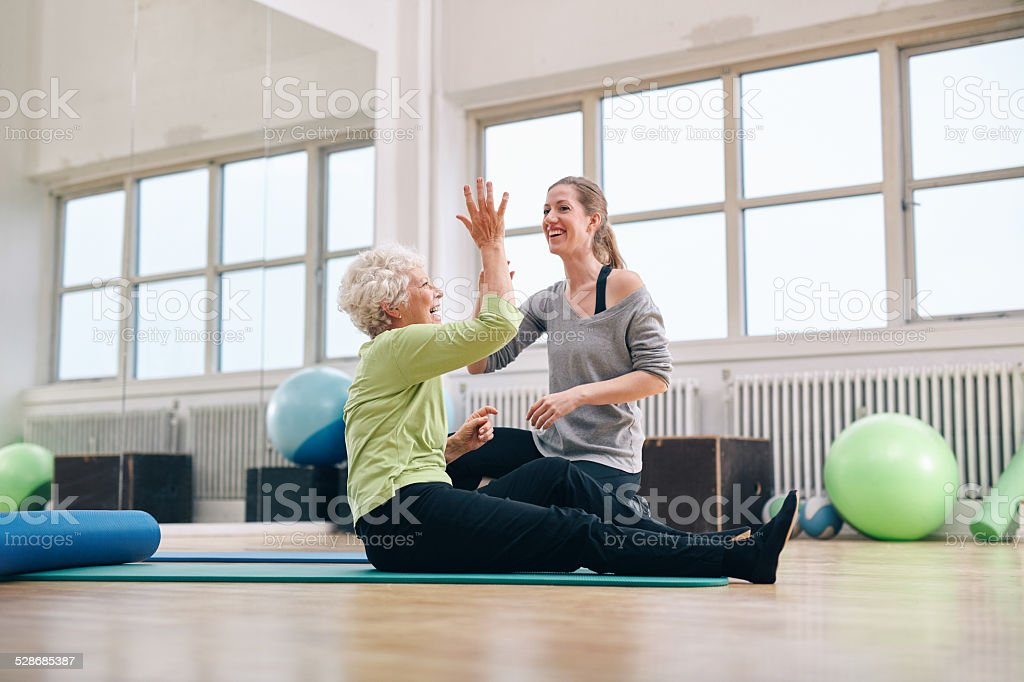 Happy elder woman rejoicing health success with her trainer stock photo