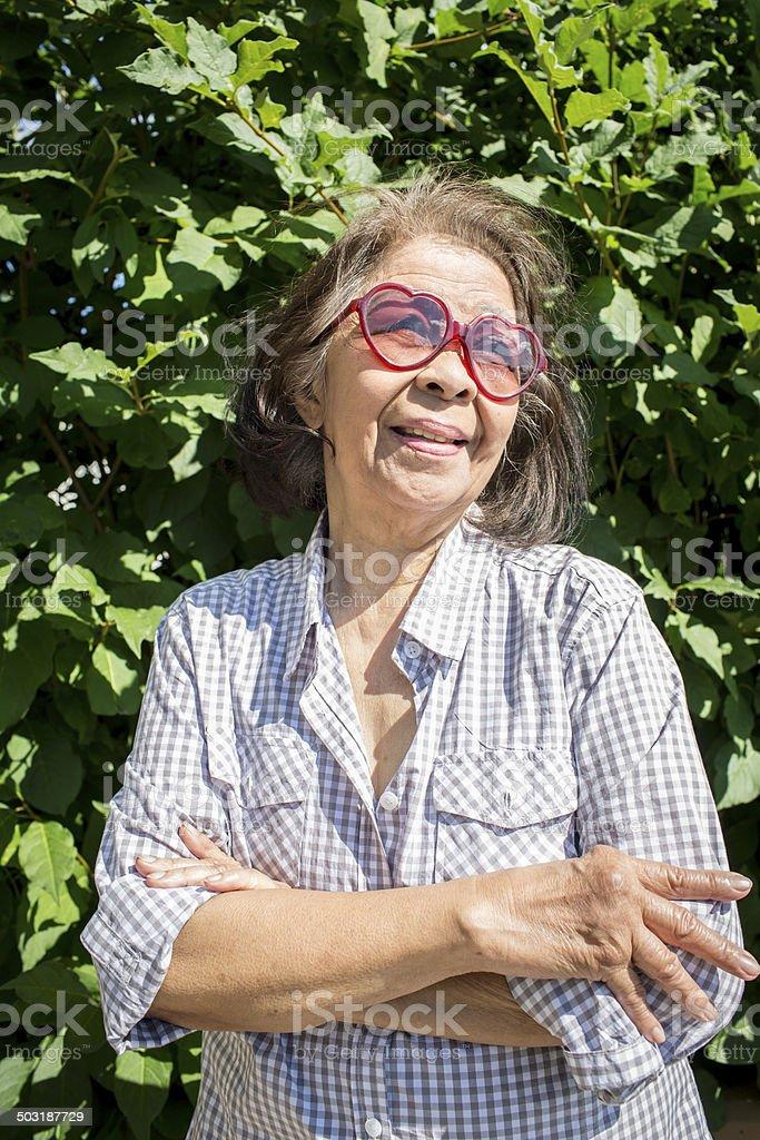 Happy elderly Asian woman wearing heart shape sunglasses royalty-free stock photo