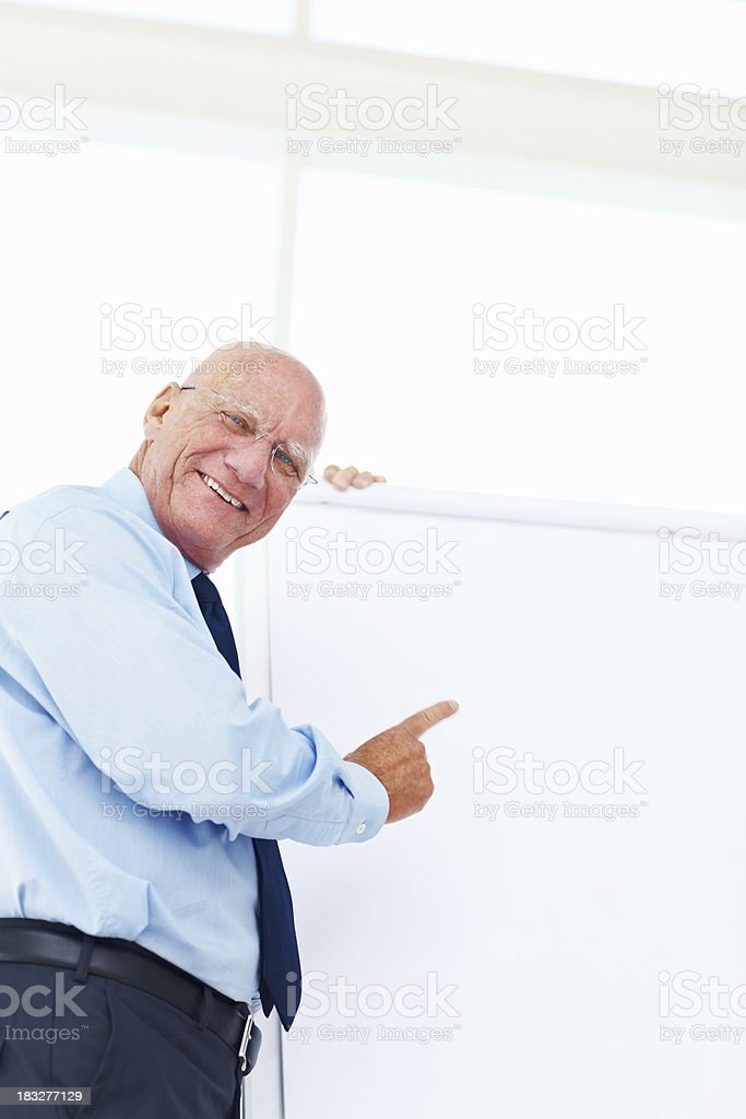 Happy elderly business man pointing at white board in office royalty-free stock photo